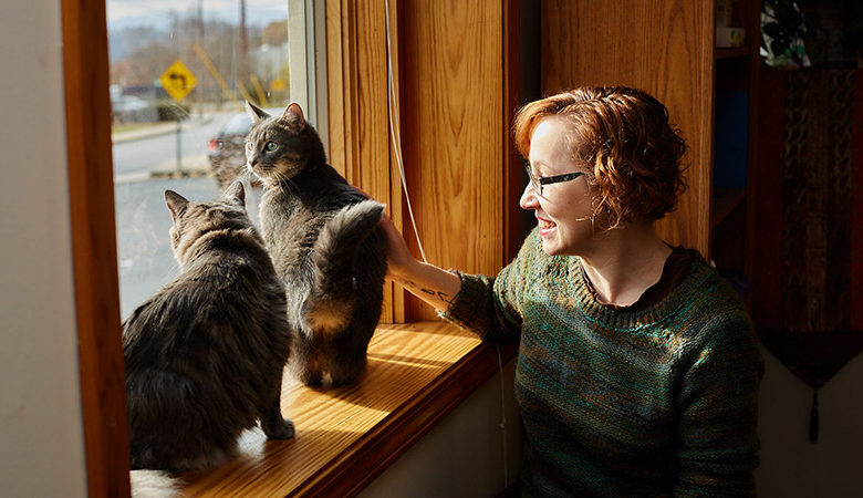 Woman looks out of window with two cats