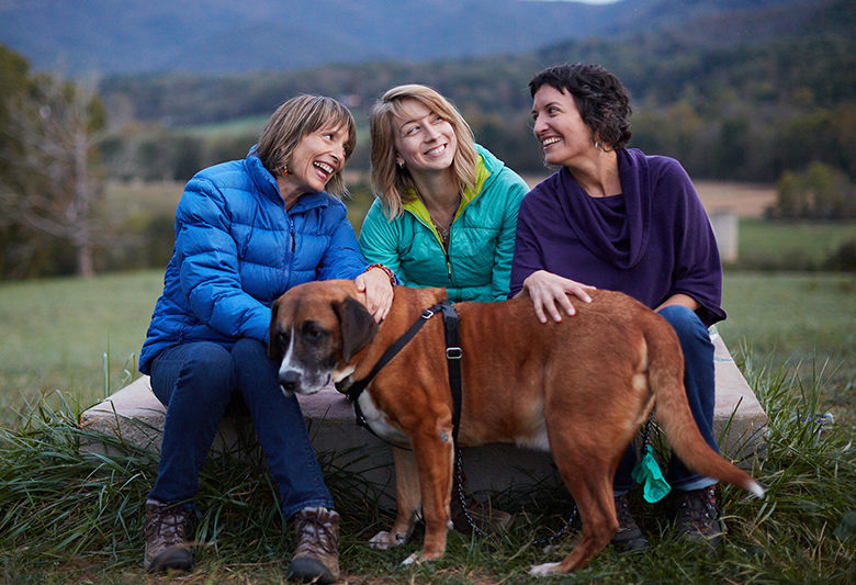 three women laugh with a dog
