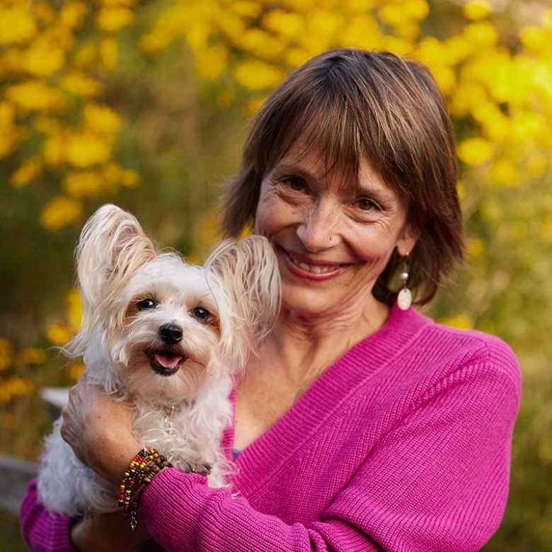 Dr. laurel Davis holds smiling white dog in yellow flowers