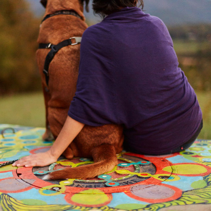 Woman with arm around dog sitting on colorful floor