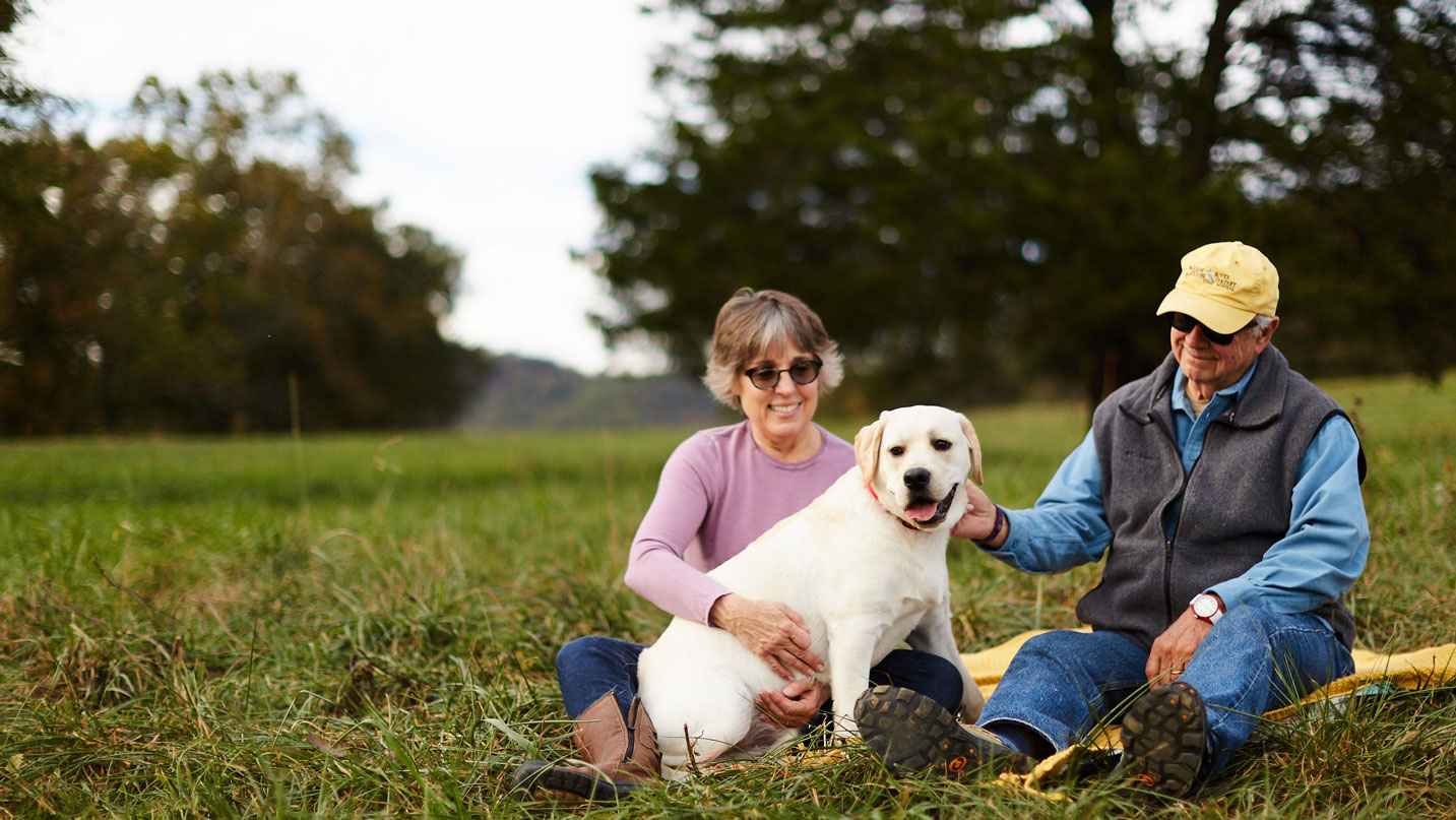 woman-and-man-sitting-in-park-with-white-lab